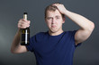 drunk man with bottle of champagne over grey