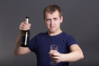 young drunk man with bottle of champagne and glass