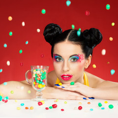 Funny woman with colorful makeup under falling candy drops