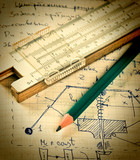 pencil and a slide rule on the old page with the calculations in