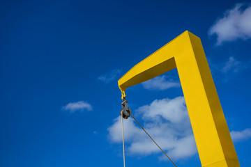 Ein gelber Kran vor blauem Himmel.