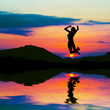 Silhouette of a happy woman jumping for joy at sunset.