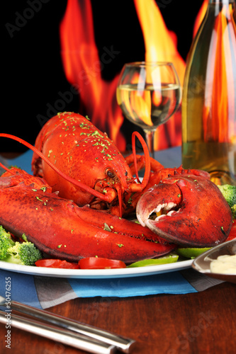 Red lobster on platter on wooden table on fire background