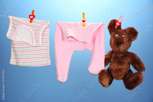 Baby clothes hanging on clothesline, on color background