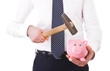 Businessman with piggy bank and hammer.