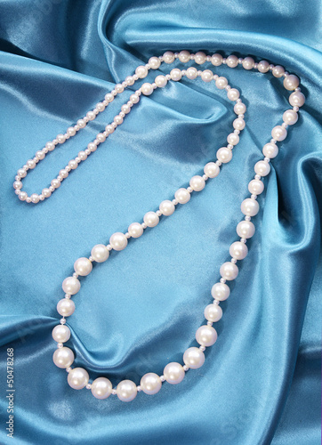 pearl necklace on turquoise silk fabric, luxury