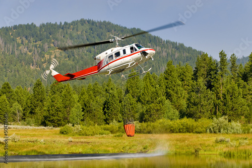 Fotobehang Helicopter Small Helicopter dips water out of a mountaiin pond
