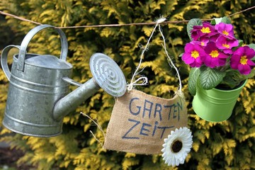 Gärtnerdeko auf Wäscheleine, grüner Hintergrund