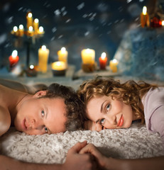 Sexy young couple lay in bed . Candles.