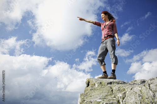 Woman standing on a mountain and gazing in the distance