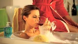 girl drinking a glass of wine in the bath tub