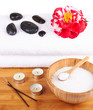 Spa setting with candles, flower, towel and stones