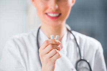 Young female dentist doctor holding chewing gum and smiling. Ora