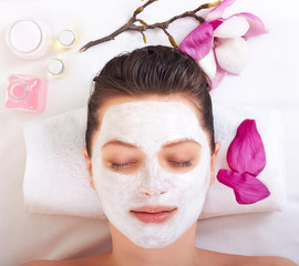 Young beautiful girl receiving pink facial mask