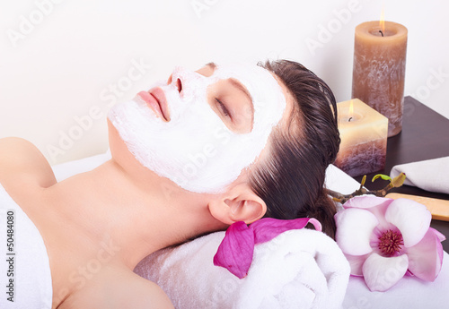 Beautiful girl receiving pink facial mask