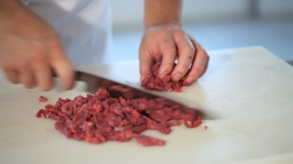 hands cutting fresh meat