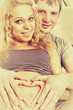 Vintage style photo with beautiful young pregnant couple