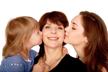 Two daughters kissing mother. Motherhood concept.