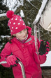 Winter cold snap. Young girl measures icicle depth