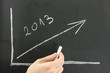 Businessman showing graph for 2013 on a board.