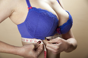 Woman using a tape measure to check under bra size