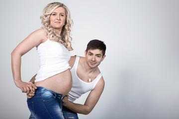 Frau mit Babybauch und Ehemann ganz Stolz