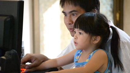 asian father teach cute daughter teach computer