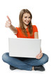 Young woman sitting on floor with her laptop making thumb up