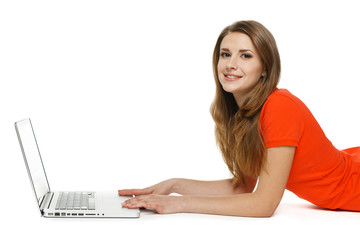 Side view of female using laptop lying on floor