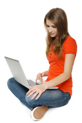 Young woman sitting on the floor while using her laptop