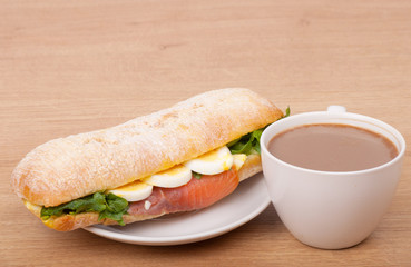 coffee cup and Real sandwich with smoked salmon, eggs and green