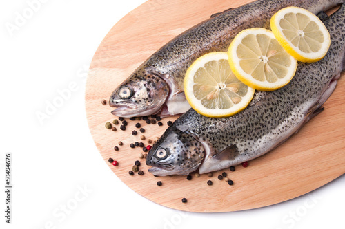 Trout on wooden plate isolated over white