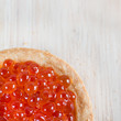 Tartlet with red caviar on light wooden background