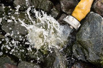 Schlauch und spritzendes Wasser