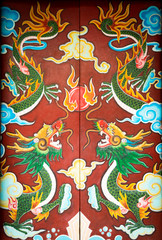 Colorful door with symmetrical dragon painting.