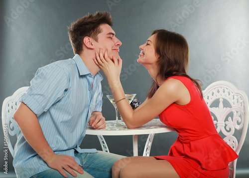 Happy young couple having romantic dinner indoors, in studio