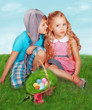 GIrl and boy wearing as Easter Rabbit sitting on the grass