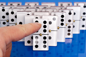 Dominoes on Blue with a Finger Pushing Them.