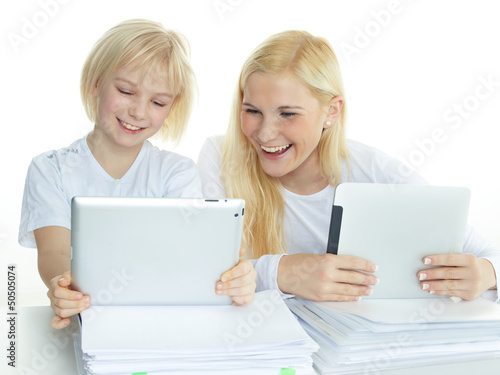 Two pupils leaning on a stack of paper while reading on touchpad