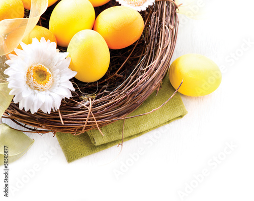 Easter. Painted Easter Eggs and Spring Flowers in the Nest