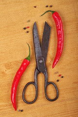 Top view on old scissors, and red hot chili peppers.