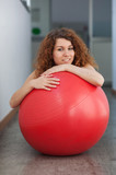 Portrait of young woman with red ball in the gym.