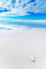 White rock in a white beach under blue and cloudy sky