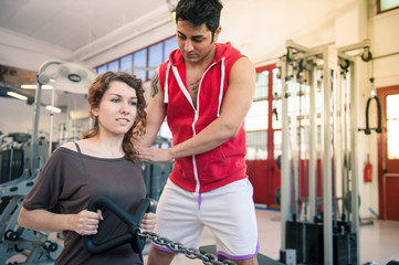 Woman exercising with her personal trainer at the gym.