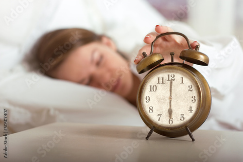 Woman's hand off the alarm clock