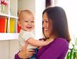 woman looking at laughing kid at home