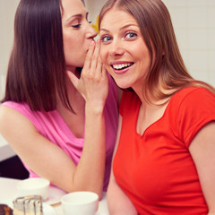 woman whispering message to her friend