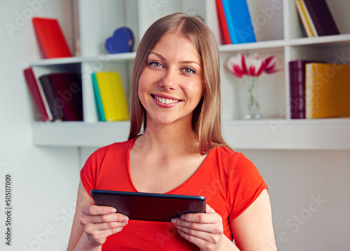 woman holding the tablet pc and looking at camera