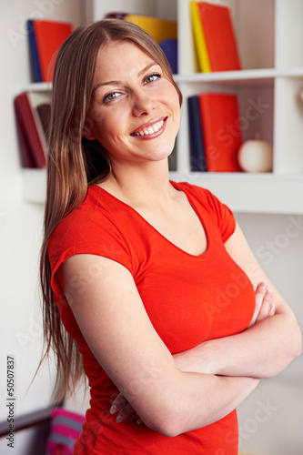 woman posing over bookshelf