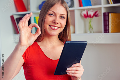 woman using the tablet pc and showing ok sign